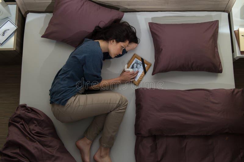Mulher de lamentação nova que encontra-se na cama fotos de stock