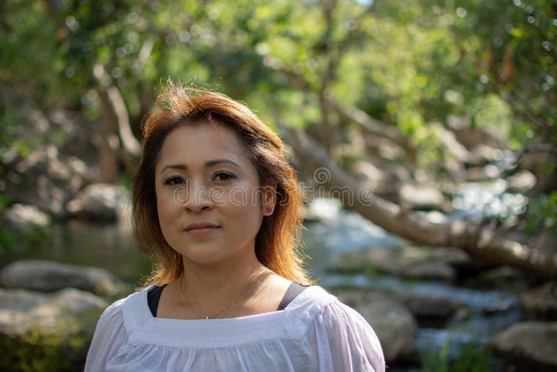 Mulher de Latina com posição séria da expressão na máscara com cabelo de incandescência em um córrego com as cachoeiras no fundo imagem de stock