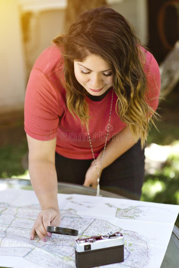 A mulher de Latina olha um mapa com uma lupa para planejar seus cursos foto de stock