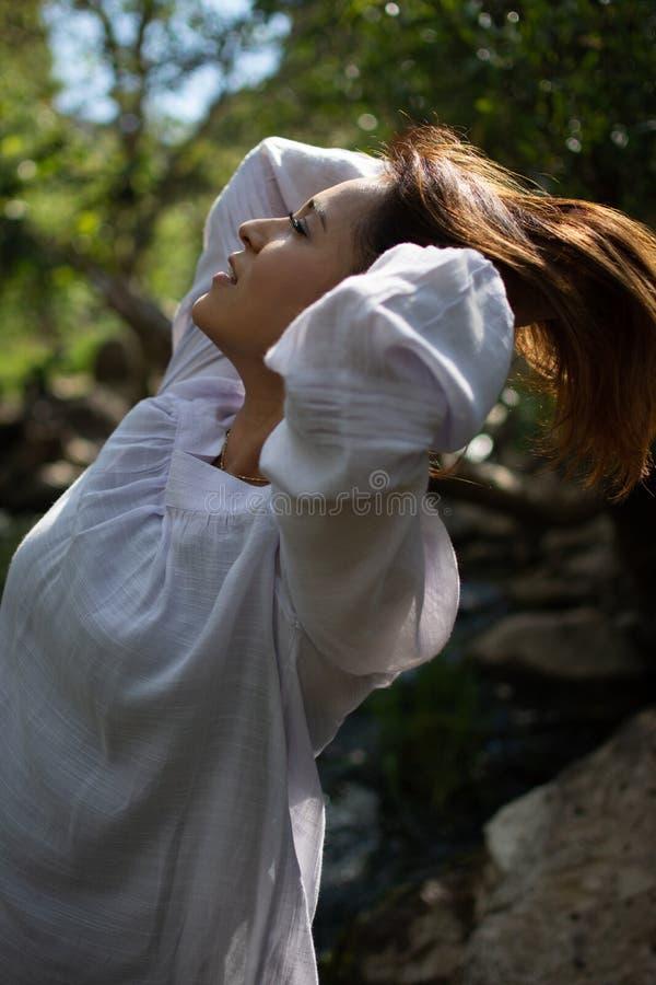Mulher de Latina que joga seu cabelo para trás com seu cabelo no sol na frente das madeiras e um córrego na máscara imagens de stock royalty free