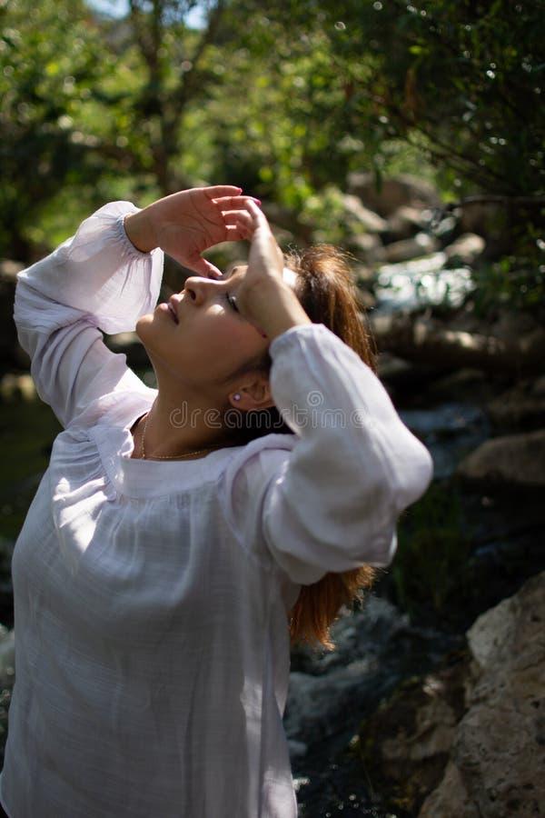 Mulher de Latina que joga seu cabelo para tr?s com seu cabelo no sol na frente das madeiras e um c?rrego na m?scara foto de stock royalty free