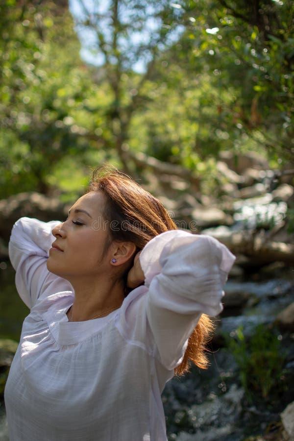 Mulher de Latina que joga seu cabelo para tr?s com seu cabelo no sol na frente das madeiras e um c?rrego na m?scara fotografia de stock royalty free