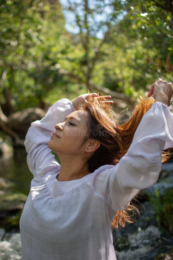 Mulher de Latina que joga seu cabelo para tr?s com seu cabelo no sol na frente das madeiras e um c?rrego na m?scara imagem de stock
