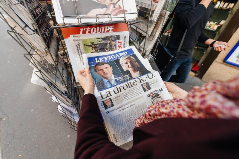 Mulher de Le Figaro que compra a imprensa internacional com Emmanuel Macron fotos de stock