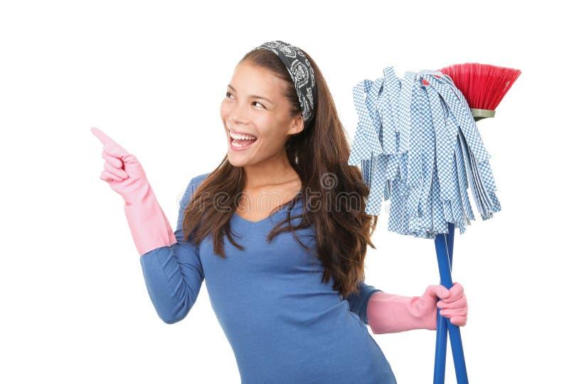 Mulher de limpeza que aponta no fundo branco foto de stock
