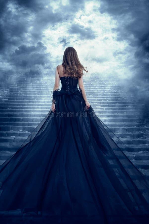 Mulher de longa distância para trás Vista sobe escadas de pedra para o céu, garota criando noite escura imagem de stock royalty free