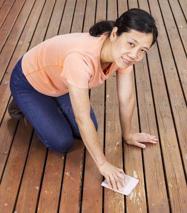 Mulher de Matue que lixa a plataforma de madeira do cedro natural à mão foto de stock