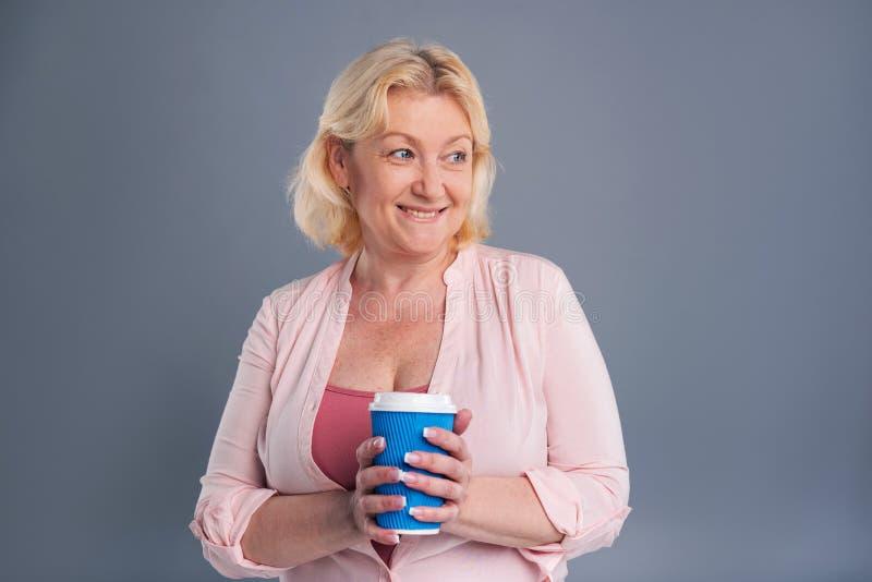 Mulher de meia idade alegre que guarda o copo de café azul fotografia de stock