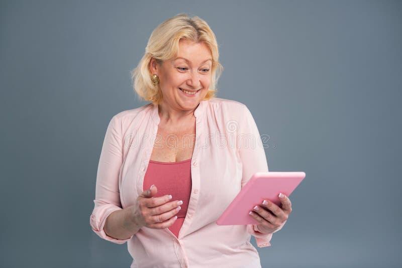 Mulher de meia idade alegre que sorri lendo a mensagem imagem de stock