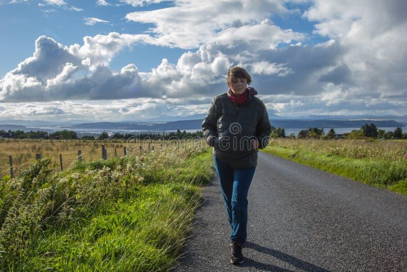 A mulher de meia idade ativa que anda ao longo da estrada para veio imagens de stock royalty free