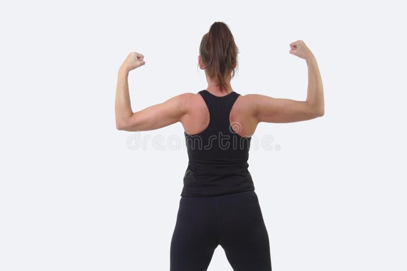 A mulher de meia idade atrativa nos esportes alinha com de volta à câmera que dobra seus músculos imagem de stock