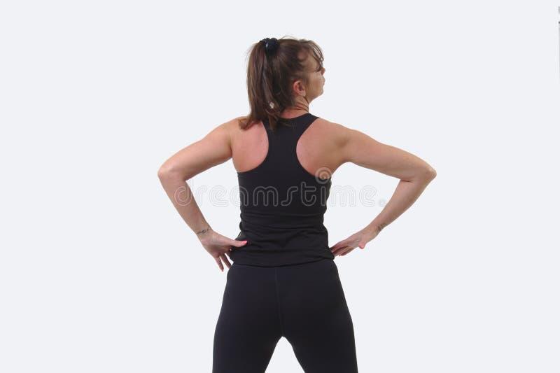 A mulher de meia idade atrativa nos esportes alinha com mãos nos quadris e de volta à câmera fotografia de stock royalty free