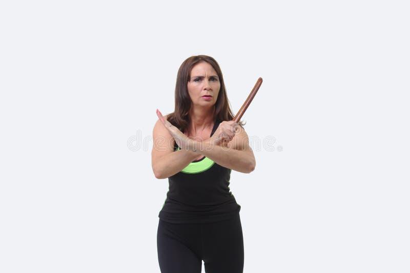 A mulher de meia idade atrativa nos esportes alinha guardar um tanto ou uma faca de madeira imagens de stock royalty free