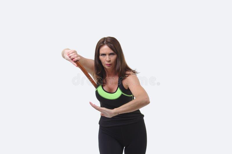 A mulher de meia idade atrativa nos esportes alinha guardar um tanto ou uma faca de madeira imagem de stock