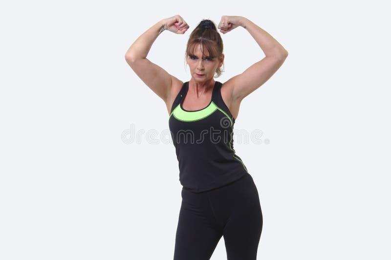 A mulher de meia idade atrativa nos esportes alinha o dobramento de seus músculos fotografia de stock royalty free