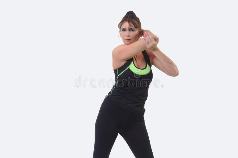 A mulher de meia idade atrativa nos esportes alinha o esticão de seu braço foto de stock royalty free