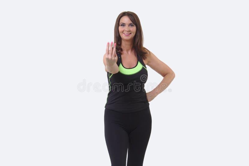 A mulher de meia idade atrativa nos esportes alinha o sorriso e a sustentação de três dedos imagem de stock royalty free