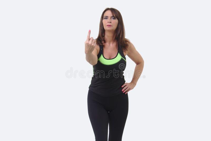 A mulher de meia idade atrativa nos esportes alinha a sustentação de um dedo imagens de stock