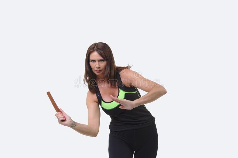 A mulher de meia idade atrativa nos esportes alinha wielding um tanto ou uma faca de madeira fotografia de stock royalty free