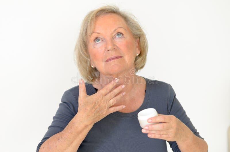 Mulher de meia idade atrativa que aplica a nata fotografia de stock royalty free