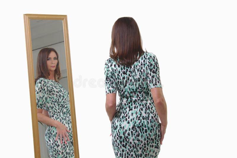 Mulher de meia idade atrativa que olha a reflexão no espelho fotografia de stock royalty free