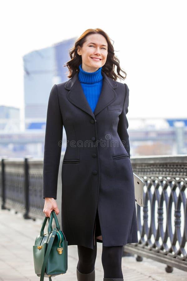 Mulher de meia idade bonita alegre em um revestimento escuro com uma bolsa verde e um portátil fotografia de stock royalty free