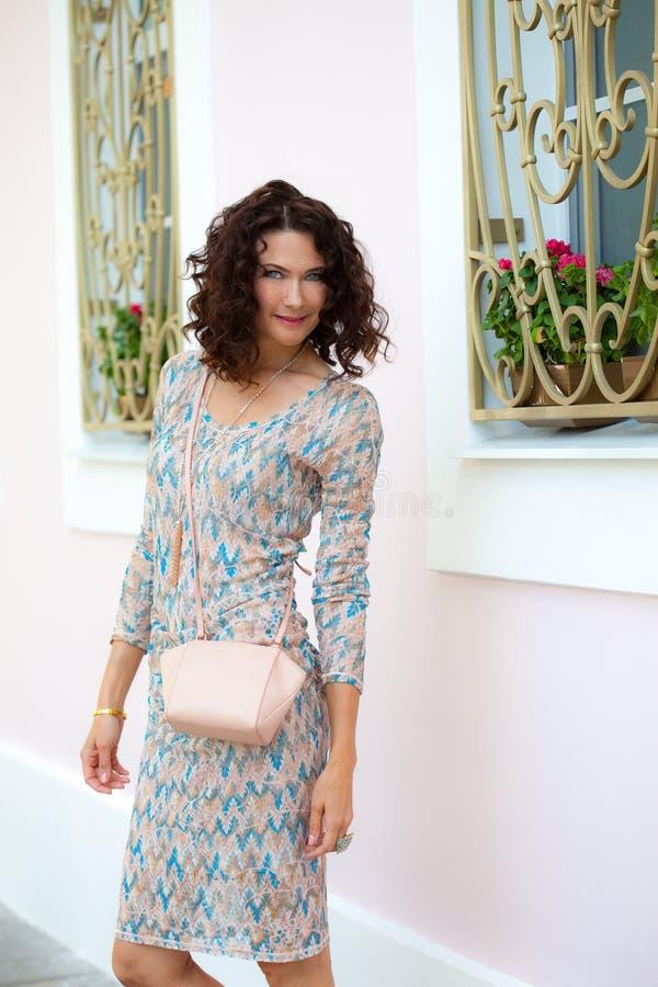 Mulher de meia idade bonita com uma bolsa bege foto de stock
