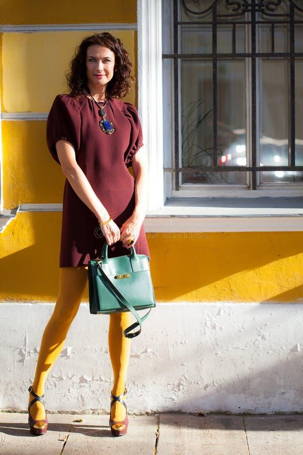 Mulher de meia idade bonita em um vestido de Borgonha com uma bolsa verde perto da parede antiga fotografia de stock royalty free