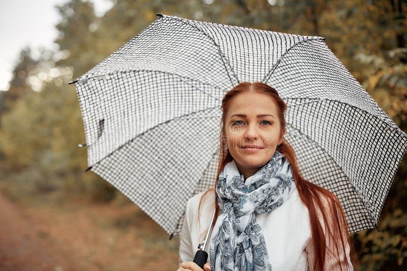 Mulher de meia idade caucasiano bonita com cabelo vermelho com um guarda-chuva no parque em um dia nebuloso do outono imagem de stock