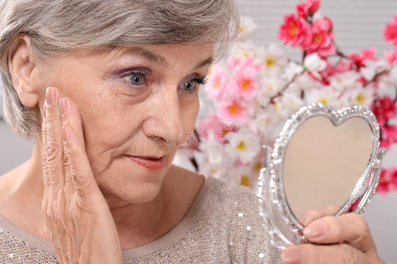 mulher de meia idade com espelho imagens de stock royalty free