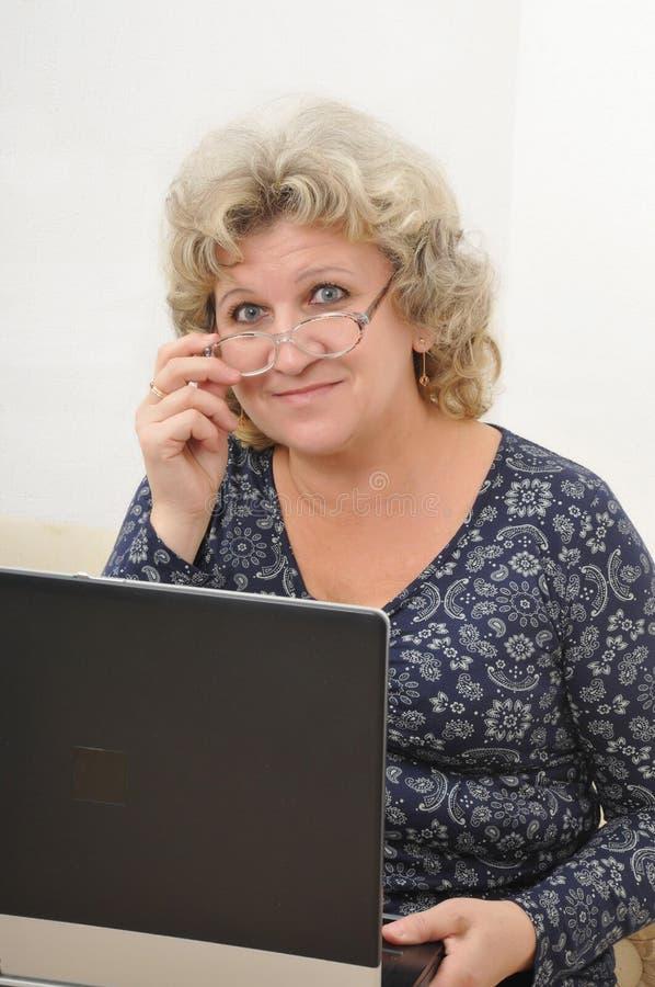 Mulher de meia idade com um portátil fotografia de stock