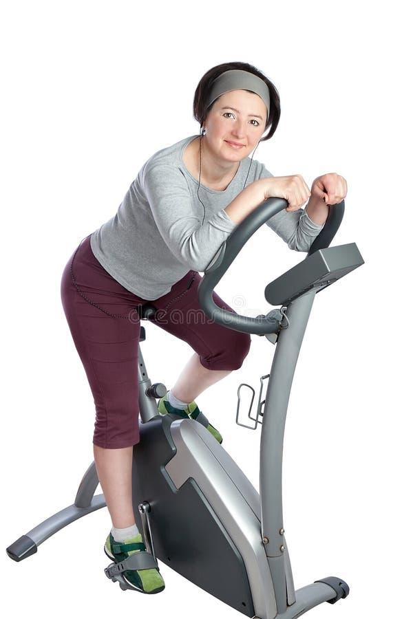 Mulher, de meia idade em uma bicicleta estacionária. imagem de stock