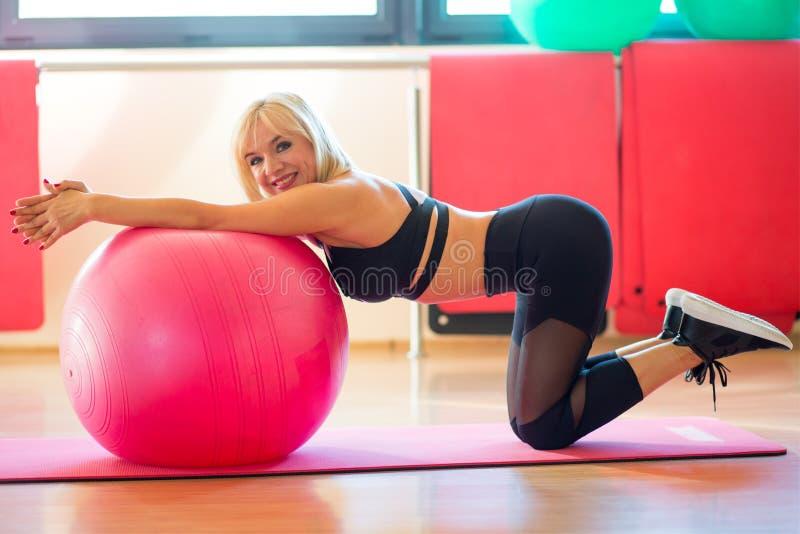 A mulher de meia idade faz exercícios com um fitball em um fitness center imagens de stock royalty free