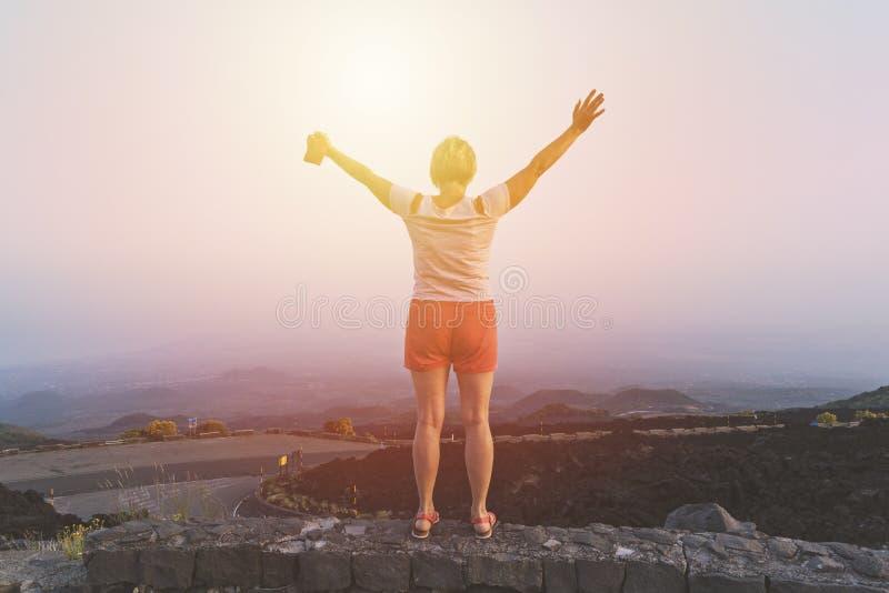 Mulher de meia idade feliz com mãos levantadas que aprecia o por do sol imagens de stock