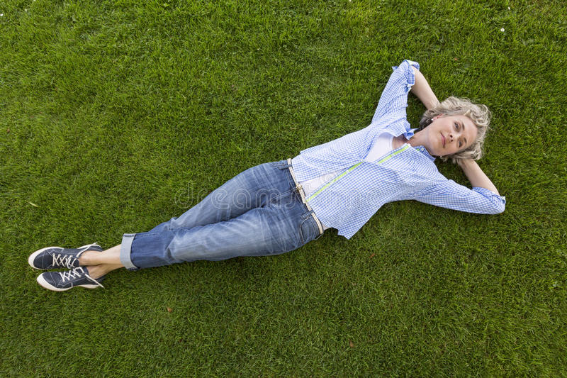 Mulher de meia idade feliz na roupa ocasional do fim de semana que relaxa na grama em um parque imagens de stock royalty free