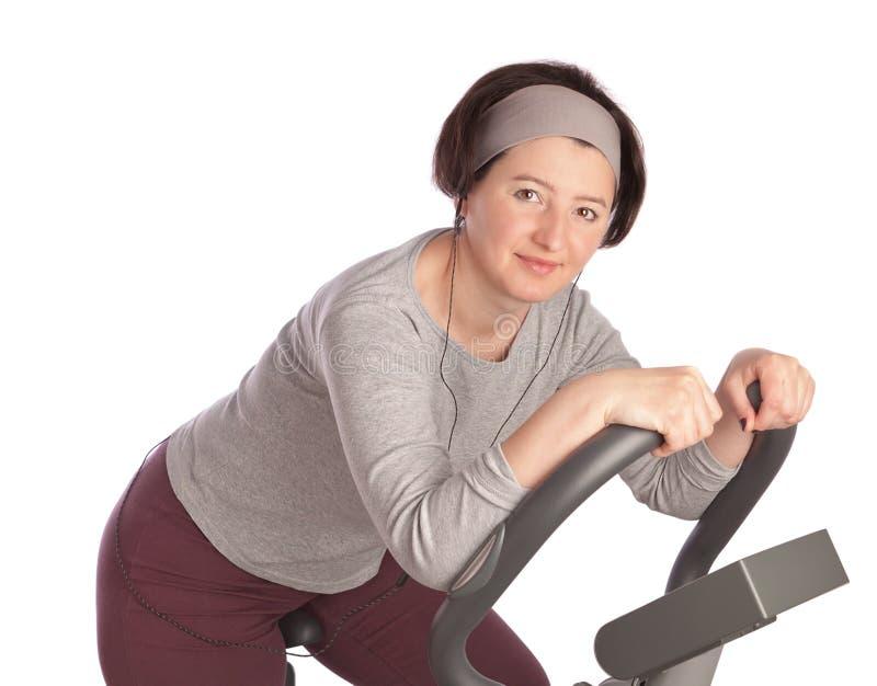 Mulher de meia idade grossa no gym em uma bicicleta estacionária. foto de stock royalty free