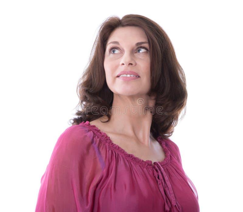 Mulher de meia idade isolada na blusa cor-de-rosa que olham lateral ou no aw imagem de stock