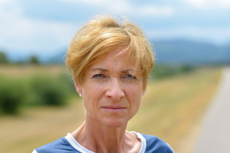Mulher de meia idade loura bonita séria fotografia de stock