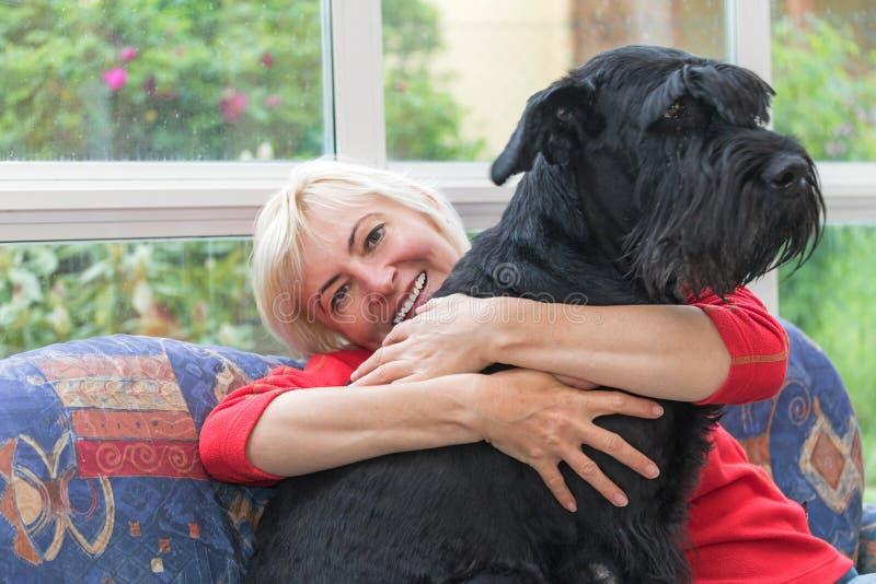 A mulher de meia idade loura está abraçando o cão imagem de stock