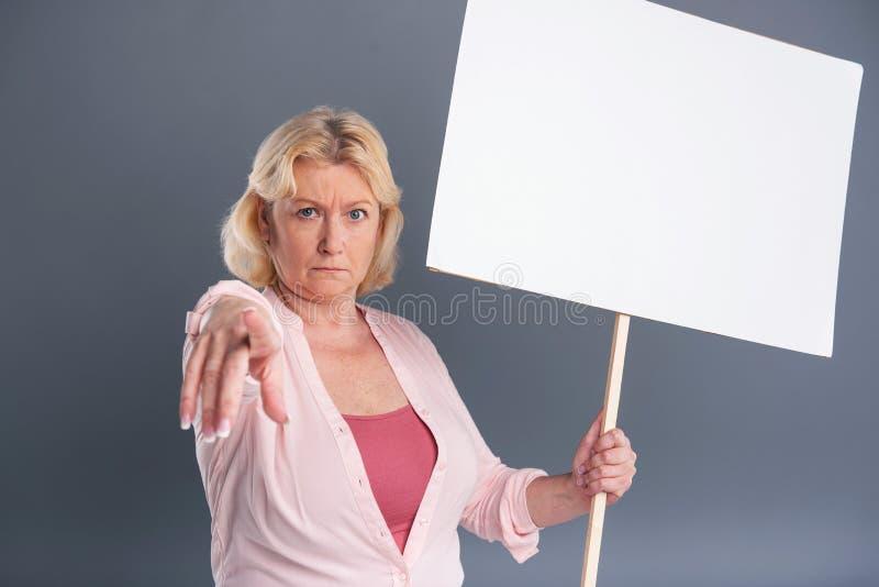 Mulher de meia idade louro que guarda a bandeira e apontar fotos de stock royalty free