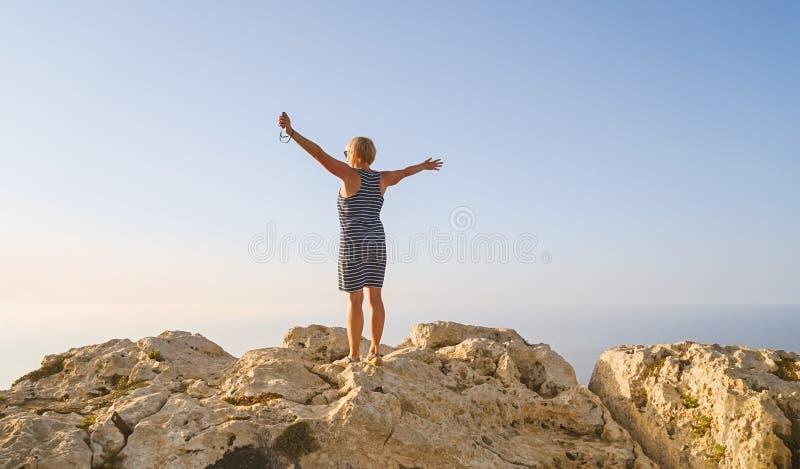 A mulher de meia idade no vestido azul cumprimenta o alvorecer do sol imagens de stock