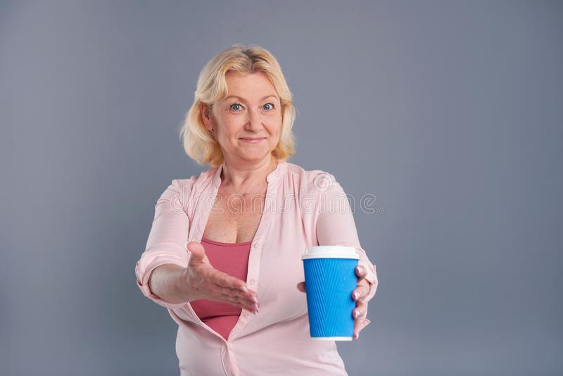 Mulher de meia idade otimista que aponta no copo de café foto de stock royalty free