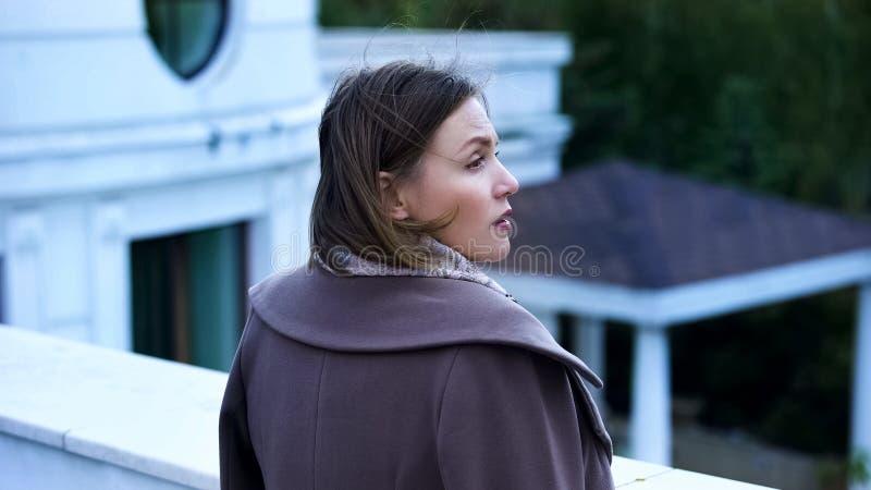 Mulher de meia idade pensativa que está no balcão da propriedade, sentindo triste e só fotos de stock