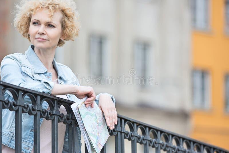 Mulher de meia idade pensativa que guarda o mapa ao inclinar-se no cerco fotografia de stock