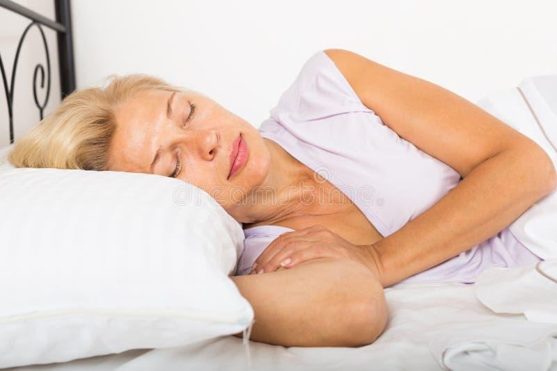 Mulher de meia idade que dorme na cama fotografia de stock