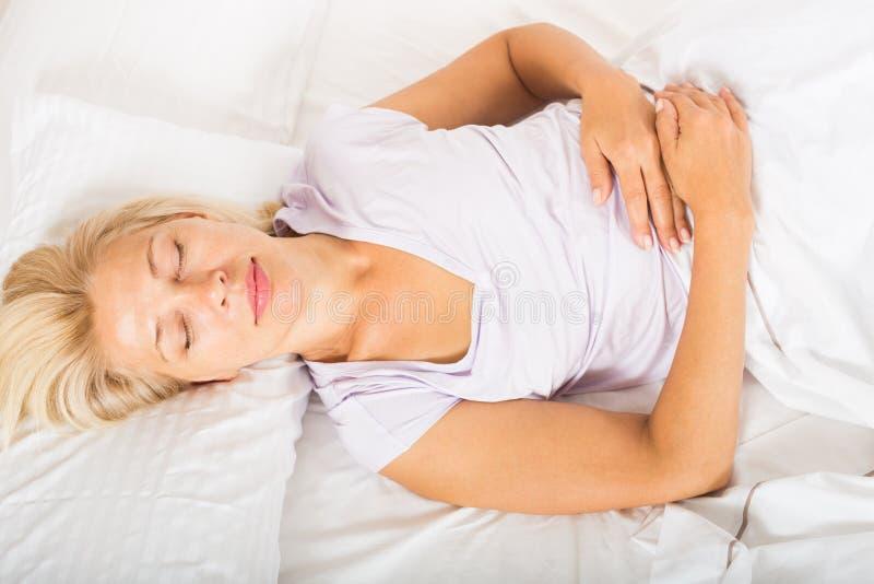 Mulher de meia idade que dorme na cama imagem de stock