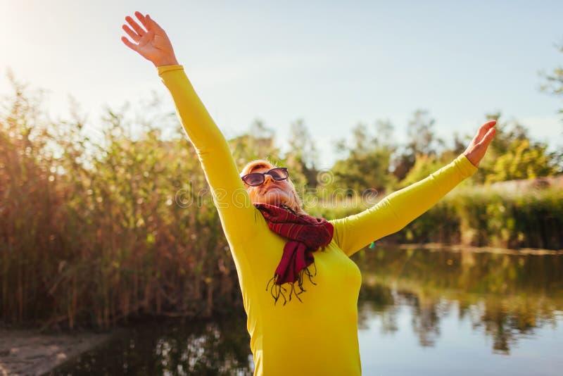 Mulher de meia idade que sente livre e feliz no banco de rio no dia do outono Senhora superior que levanta as mãos acima fotos de stock royalty free