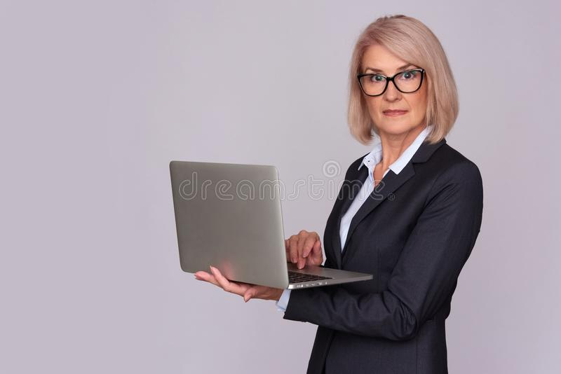 Mulher de meia idade que trabalha no portátil fotos de stock royalty free