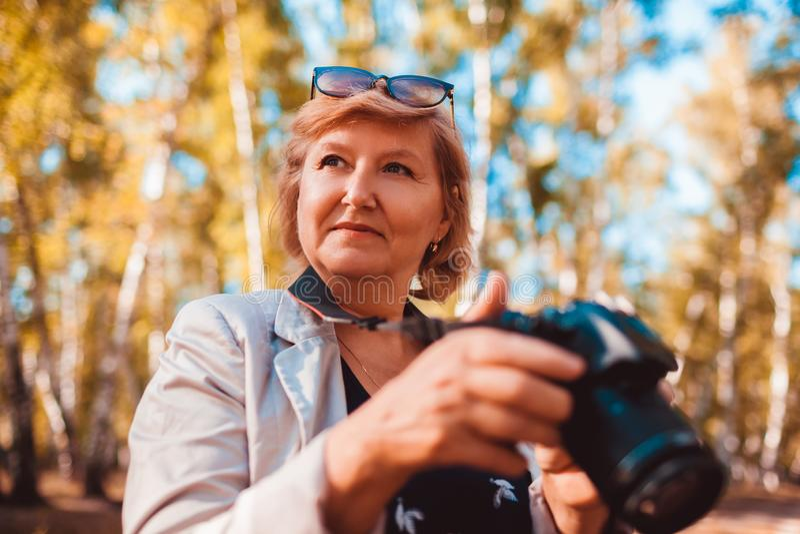 Mulher de meia idade que verifica imagens na câmera na mulher superior da floresta do outono que anda e que aprecia o passatempo fotografia de stock