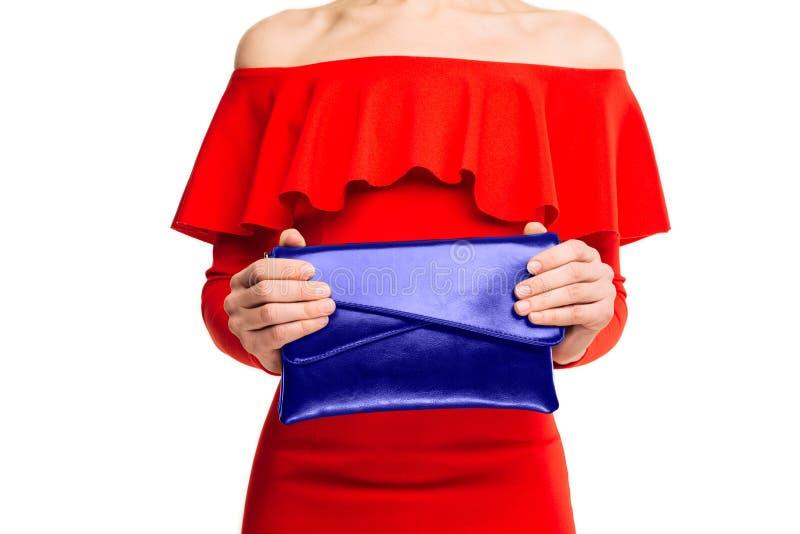 Mulher de negócio à moda em um vestido vermelho que guarda uma embreagem azul da forma foto de stock